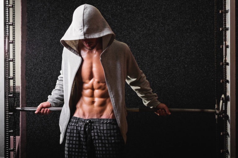 Muscular young man in gray hoodie in gym